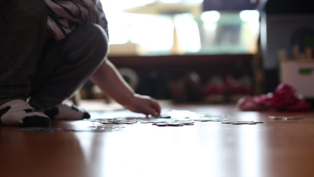 The hands of a young girl doing a puzzle on the ground inside of a home.