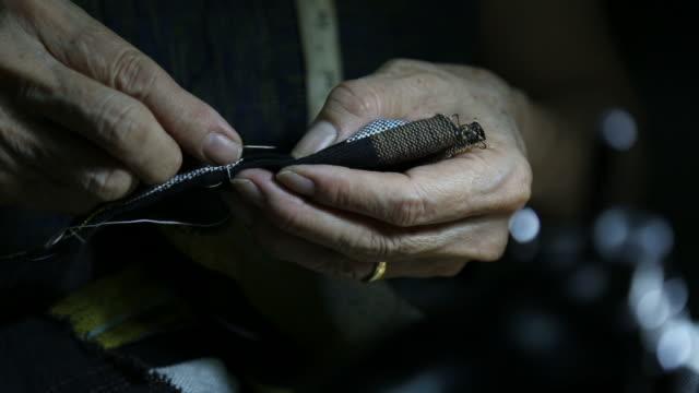 vídeos de stock, filmes e b-roll de nas mãos de uma mulher idosa costura desgaste ocasional com agulha de costura no quarto escuro. - figura feminina