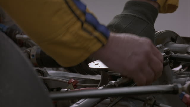 The hands of pit-crew members adjust a race car engine.