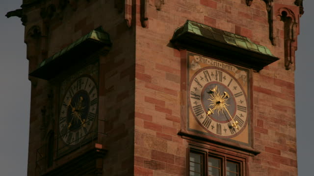 the hands on the clock tower clock above the city hall in saarbruecken, germany move as day turns to night. - clock tower stock videos and b-roll footage