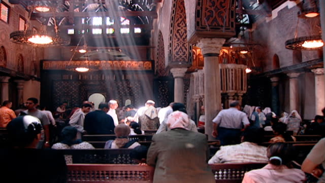 the hanging church view of shafts of light illuminating the congregation in cairo's most famous coptic church - sunbeam stock videos & royalty-free footage
