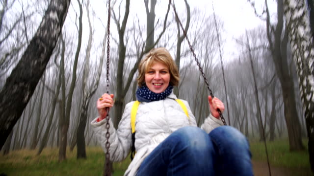 the happy beautiful active attractive 50-years-old mature woman swinging on the swings in the park - 50 54 years stock videos & royalty-free footage