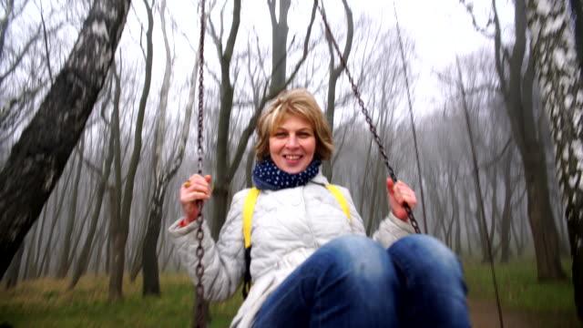 vídeos y material grabado en eventos de stock de el feliz hermosa activa 50 años madura mujer atractiva en los columpios en el parque - 50 54 years
