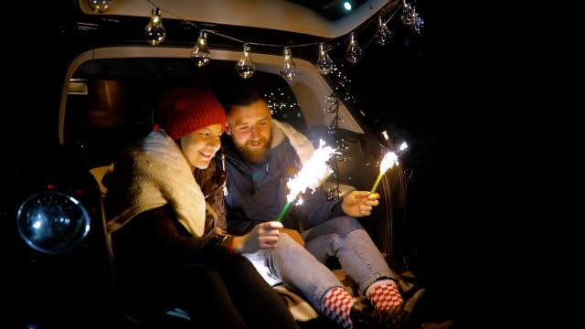 幸せなカップルは、花火の棒を保持します。夕方夜の時間