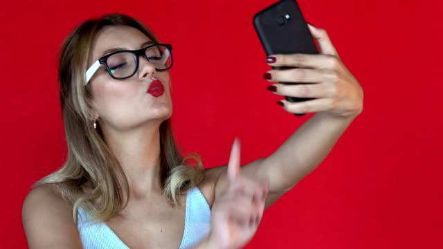 vidéos et rushes de 4k la femme heureuse est selfie - fond rouge - fond coloré