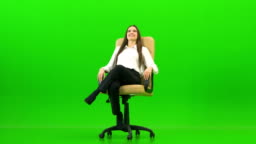 The happy woman turning on the office chair on the green background