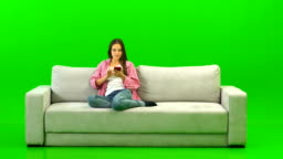The happy woman with a phone sitting on the sofa on the green background
