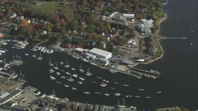 AERIAL The harbor, with marina, docked windjammers, and anchored boats in lines / Camden, Maine, United States