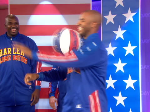 the harlem globetrotters show off their basketball and comedy skills with bright smiles to the camera. the harlem globetrotters are an exhibition... - ハーレムグローブトロッターズ点の映像素材/bロール