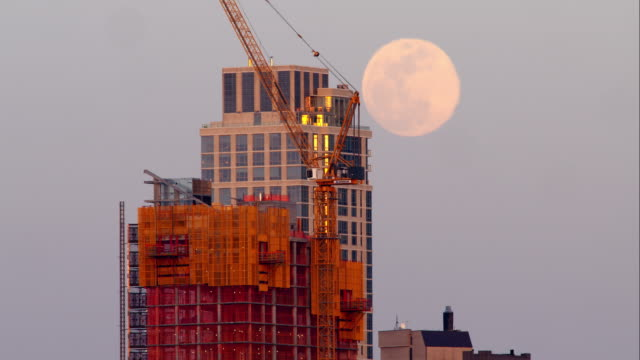 The hazy full moon rises behind tall buildings early evening before sunset.