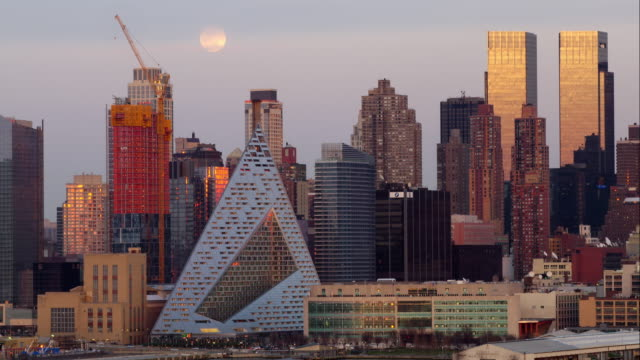 The hazy full moon rises behind the Upper Midtown skyline.