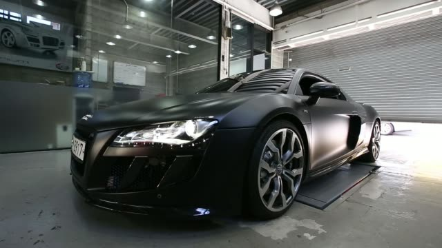 the headlight of a customized volkswagen ag audi r8 vehicle is illuminated at the a seung automotive group garage in seoul south korea on monday july... - repair garage stock videos & royalty-free footage