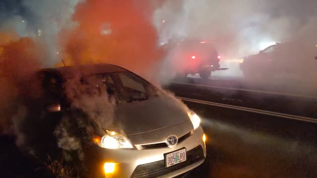the headlights of a car blink on and off with the horn as tear gas fills the parameter between traffic and police while oregon state troopers and... - portland oregon stock videos & royalty-free footage