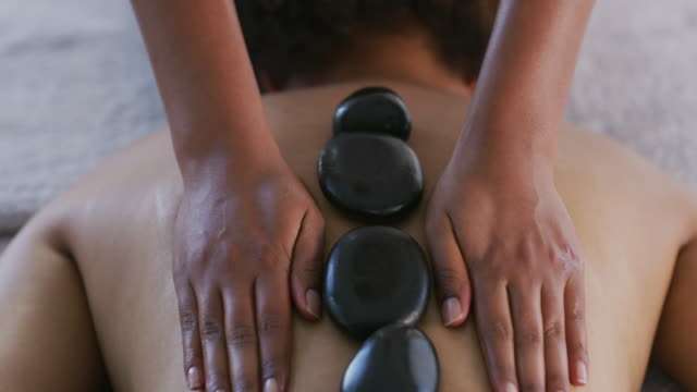 the heat from the stones is what relaxes you - spa treatment stock videos & royalty-free footage