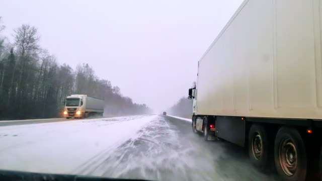 vídeos de stock e filmes b-roll de the heavy cargo trucks driving on the highway in the terrible snowy windy weather. the view through the windshield - driver point of view. mobile video. - gelo