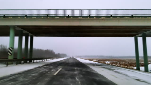 The heavy cargo trucks driving on the highway in the terrible snowy windy weather. The view through the windshield - Driver Point Of View. Mobile video.