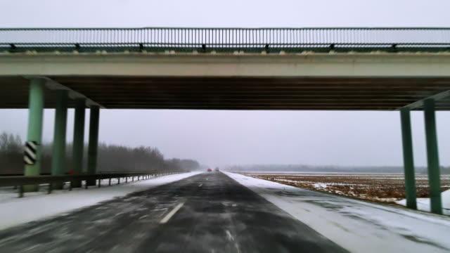 die schwere ladung lkw fahren auf der autobahn in die schreckliche windigem schneewetter. der blick durch die windschutzscheibe - fahrersicht. mobile video. - gefrorenes wasser stock-videos und b-roll-filmmaterial