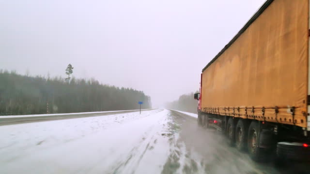 the heavy cargo trucks driving on the highway in the terrible snowy windy weather. the view through the windshield - driver point of view. mobile video. - haulage stock videos & royalty-free footage
