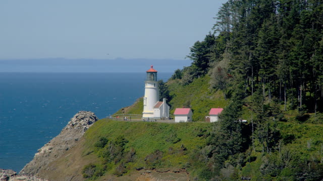the heceta head lighthouse flashes on a hillside overlooking the pacific ocean. - heceta head stock videos & royalty-free footage