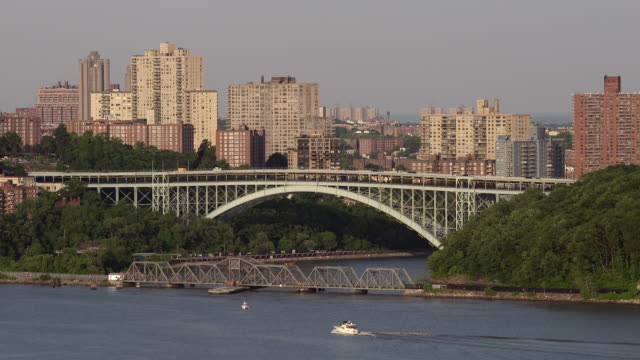 ws of the henry hudson steel arch bridge connecting upper manhattan to riverdale.  the bridge crosses the spuyten duyvil creek and is the northern most tip of manhattan.  a rail road draw bridge is in front and the riverdale skyline is behind. - arch bridge stock videos & royalty-free footage