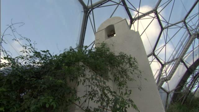 vídeos y material grabado en eventos de stock de the hexagonal dome of the eden project arcs over a bell tower and growing plants. - cornwall inglaterra