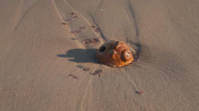 stockvideo's en b-roll-footage met de verborgen schat werd blootgelegd door de oceaan. de vintage antieke spaarpot en munten in de branding op een strand. golven komen en weg, het verlaten van de munt bank en geld op het zand. - archeologie