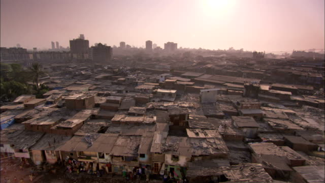 The high-rises of Mumbai tower behind the squalid houses of Dharavi. Available in HD.
