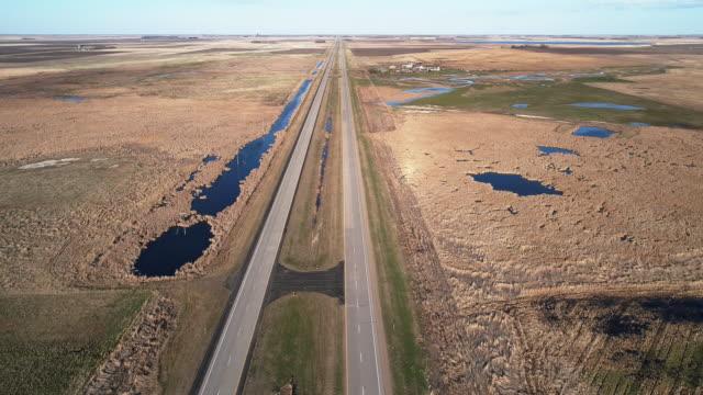 vidéos et rushes de l'autoroute 2 dans les champs du dakota du nord au printemps. vidéo drone aérien avec le mouvement de la caméra arrière. - dakota du nord