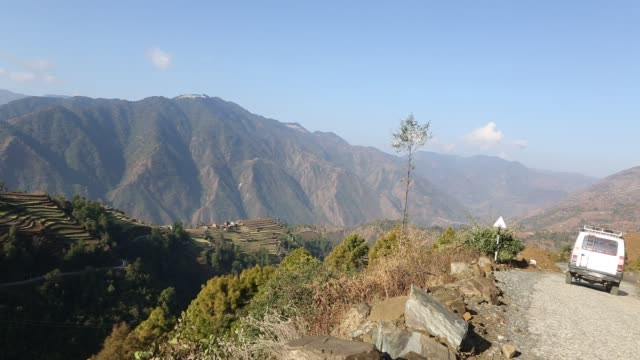 WS PAN of the hillside in the mountains near Kathmandu Nepal while an offroad vehicle is passing by and driving down a narrow rocky road