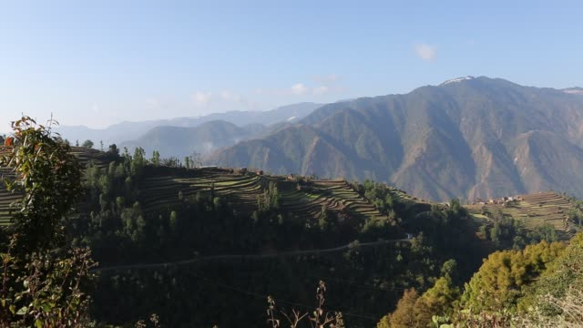 WS PAN of the hillside in the mountains near Kathmandu Nepal with several small huts that were built on the hills can be seen in the distance as well