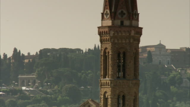 the hillsides of florence are visible behind the steeple and bell tower of the basilica di santa maria del fiore. available in hd. - steeple stock videos & royalty-free footage