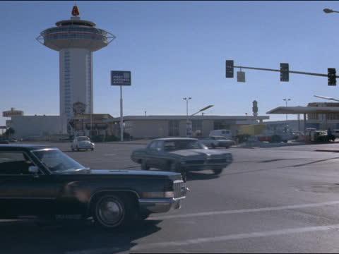 the hilton hotel rises above the las vegas strip. - las vegas hilton stock-videos und b-roll-filmmaterial