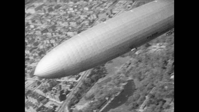 / the hindenburg airship flies high above the city and countryside / cu zeppelin with the houses dotting the landscape below hindenburg airship flies... - airship stock videos & royalty-free footage