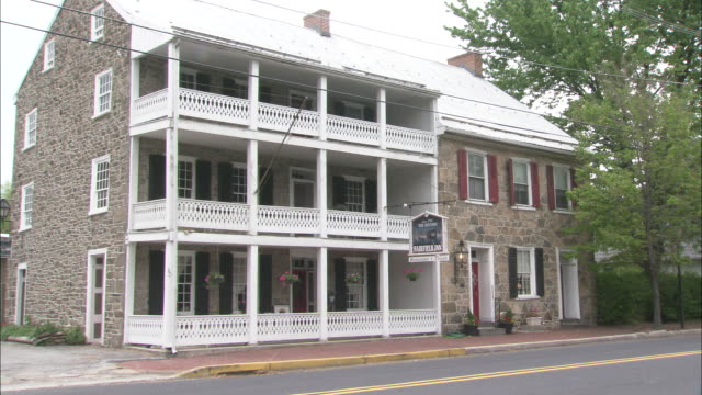 the historic fairfield inn in gettysburg, pennsylvania,  features a stone facade and two levels of white balconies. - gettysburg stock videos & royalty-free footage