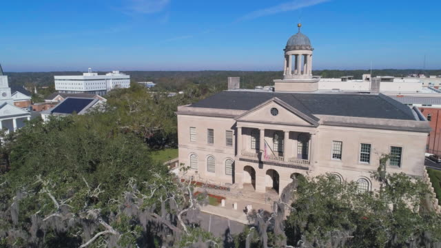 the historic united states courthouse building, tallahassee. the old trees covered by spanish moss in front. aerial drone video with the descending and tilting-up complex camera motion. - courthouse stock videos & royalty-free footage