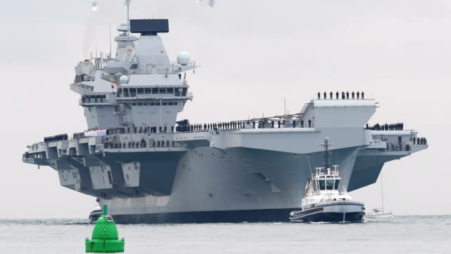 the hms queen elizabeth supercarrier heads into port on august 16 2017 in portsmouth england the hms queen elizabeth is the lead ship in the new... - british military stock videos & royalty-free footage