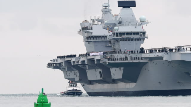 the hms queen elizabeth supercarrier heads into port on august 16 2017 in portsmouth england the hms queen elizabeth is the lead ship in the new... - aircraft carrier stock videos and b-roll footage