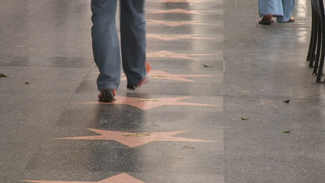 vídeos de stock e filmes b-roll de the hollywood boulevard walk of fame with people walking by - bulevar