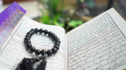 The Holy Book Koran and rosary on the table