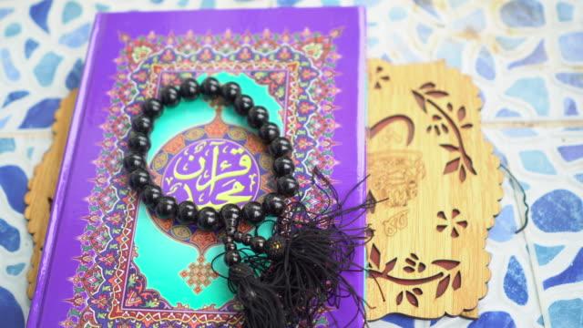 テーブルの上の聖典コーランとロザリオ - 聖典 コーラン点の映像素材/bロール