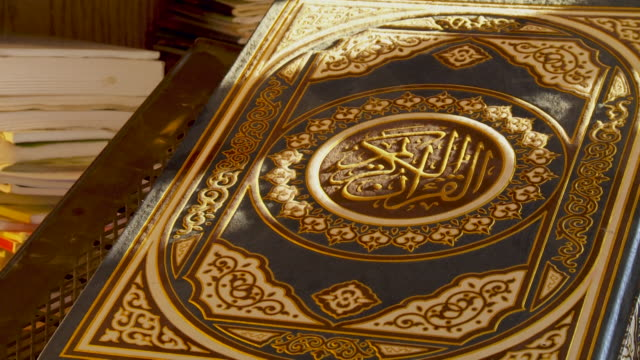 the holy quran panright across an embossed book decorated with a green and gold foliate design holy quran is written in the centre - koran stock videos & royalty-free footage