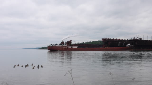 the hon james l oberstar self discharging bulk carrier changes positions as it is loaded with taconite pellts at two harbors iron ore docks in two... - lago superiore video stock e b–roll
