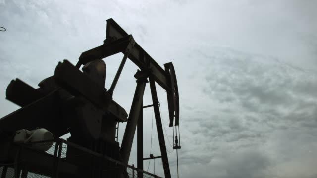 vídeos de stock, filmes e b-roll de o feixe de cavalo e caminhada de um bombeador de óleo bobs para cima e para baixo em silhueta contra um céu nublado como ele bombeia óleo debaixo do chão - boca de poço