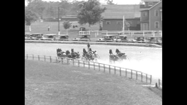 VS the horses walk on the track with the grandstands behind them the race starts and they run forward and pass the camera a long pan of the race and...