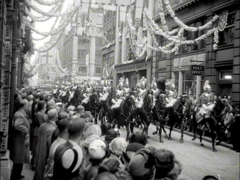 stockvideo's en b-roll-footage met the household cavalry ride their horses along a street towards the guildhall 1953 - militair uniform