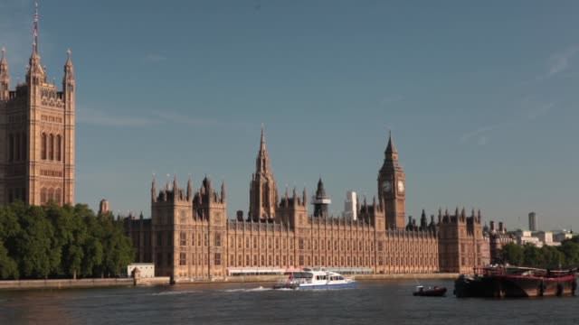the houses of parliament stand on the banks of the river thames in london, u k, on monday, july 15 tilt down from blue sky to houses of parliament... - ランベス点の映像素材/bロール