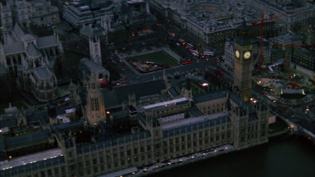 the houses of parliament with big ben sit on the river thames in london. - clock tower stock videos & royalty-free footage