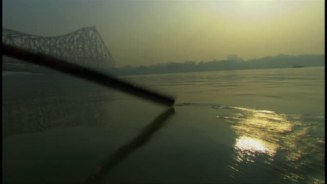 the howrah bridge from a rowboat. - howrah bridge stock videos and b-roll footage