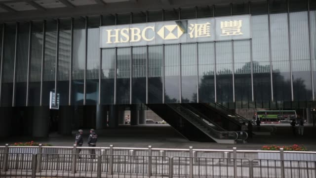 the hsbc holdings plc logo is displayed at the hsbc headquarters main building as security guards stand beneath in hong kong hsbc sign on exterior of... - hsbc main building stock videos and b-roll footage