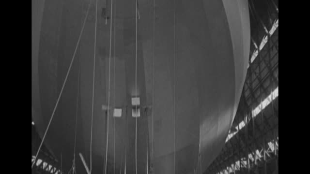 vs the huge airship r101 in its hangar and the nose of the craft is at the open door / people gathered around one of the ship's motors and propeller... - airship stock videos & royalty-free footage